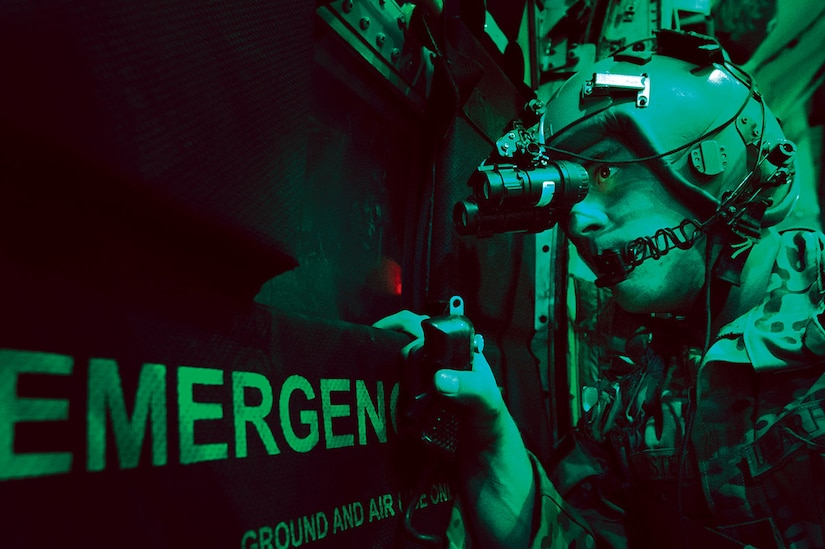 U.S. Air Force Senior Airman Larry Webster, a loadmaster with the 774th Expeditionary Airlift Squadron, scans for threats using night vision goggles aboard a C-130H Hercules aircraft after completing a cargo airdrop mission over Ghazni province, Afghanistan, Oct. 7, 2013. (DoD photo by Master Sgt. Ben Bloker, U.S. Air Force/Released)