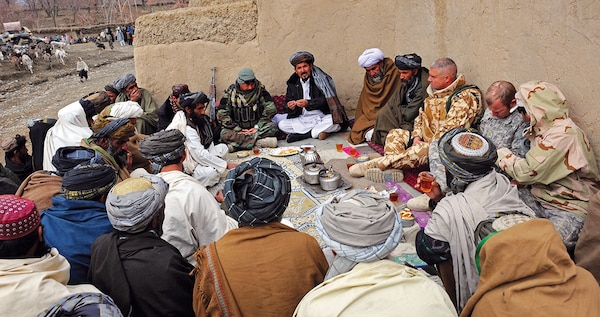 In 2011, Afghan government and International Security Assistance Force officials take part in a shura with elders in Zabul province, Afghanistan. The Zabul Provincial Reconstruction Team visited the village to talk with elders and help Afghan National Security Forces distribute winter supplies. (U.S. Air Force/Brian Ferguson)