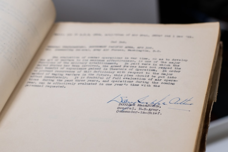 An Air University Library employee holds a historical document signed by former Commander-in-Chief, U.S. Army Gen. Douglas MacArthur, Aug. 22, 2019, on Maxwell Air Force Base, Alabama. This document is just one of many historical products the Air University Library is digitizing, making it available to DOD employees, regardless of location.