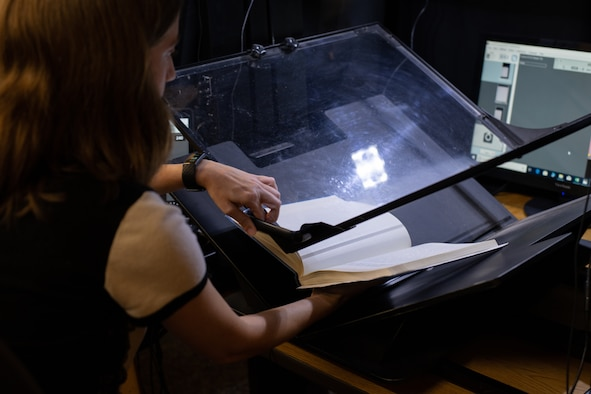 Alexandra Aldridge, Air University Library employee, demonstrates one of the digitization methods the library is using to make their resources available DOD-wide, Aug. 22, 2019, on Maxwell Air Force Base, Alabama. The AUL is currently working on digitizing more than 2,500 linear feet of resources, providing the larger Air Force and DOD communities with access to their research and products regardless of location.
