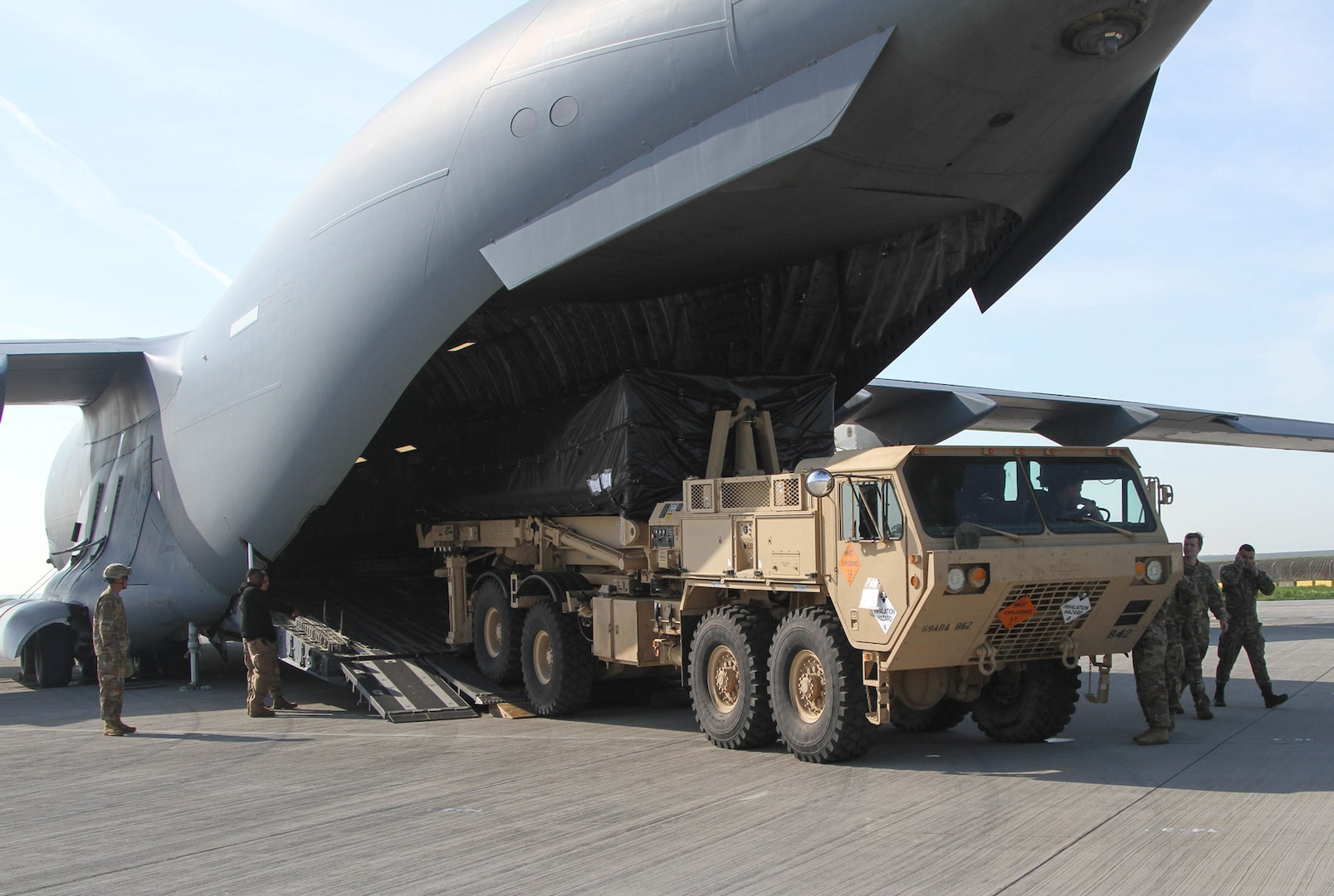 American troops offload a Terminal High Altitude Area Defense launcher from a C-17 Globemaster III