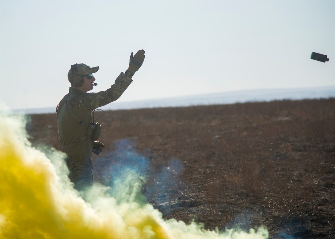 Staff Sgt. David Chorpeninng, 366th Fighter Wing survival, evasion, resistance and escape specialist, pops a M-18 smoke grenade Sept. 26, 2019, at Saylor Creek Bombing Range, Idaho.