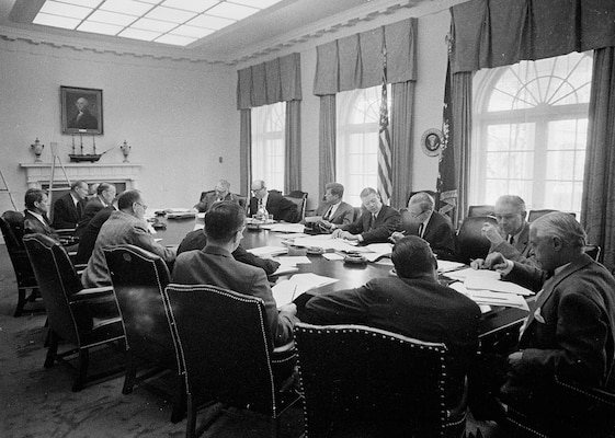"""ST-A26-1-62 29 October 1962  Meeting of the Executive Committee of the National Security Council (EXCOMM) regarding Cuba in the Cabinet Room, White House, Washington, D.C. Clockwise from top right side of table: Under Secretary of State George Ball; Secretary of State Dean Rusk; President John F. Kennedy; Secretary of Defense Robert S. McNamara; Deputy Secretary of Defense Roswell Gilpatric; Chairman of the Joint Chiefs of Staff General Maxwell Taylor; Assistant Secretary of Defense Paul Nitze; Deputy United States Information Agency  (USIA) Director Donald Wilson; Special Counsel to the President Theodore Sorensen; Special Assistant to the President for National Security McGeorge Bundy; Secretary of the Treasury C. Douglas Dillon; Vice President Lyndon B. Johnson (mostly hidden behind Dillon); Attorney General Robert F. Kennedy; former Ambassador to the Soviet Union Llewellyn Thompson; Arms Control and Disarmament Agency Director William C. Foster; Central Intelligence Agency (CIA) Director John McCone (mostly hidden behind Thompson and Foster).  Please credit """"Cecil Stoughton. White House Photographs. John F. Kennedy Presidential Library and Museum, Boston"""""""