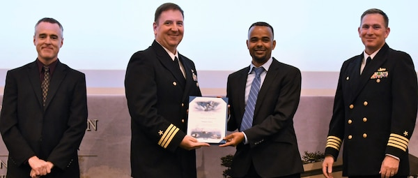 IMAGE: Mulugeta Tesfaye receives his certificate of achievement from Naval Surface Warfare Center Dahlgren Division (NSWCDD) Dam Neck Activity Commanding Officer Cmdr. Joseph Oravec at the 2019 NSWCDD academic recognition ceremony held at the University of Mary Washington Dahlgren campus. Tesfaye was congratulated at the event for completing a master's degree in cyber engineering from Morgan State University by Oravec, NSWCDD Commanding Officer Capt. Casey Plew, right, and NSWCDD Deputy Technical Director Darren Barnes.