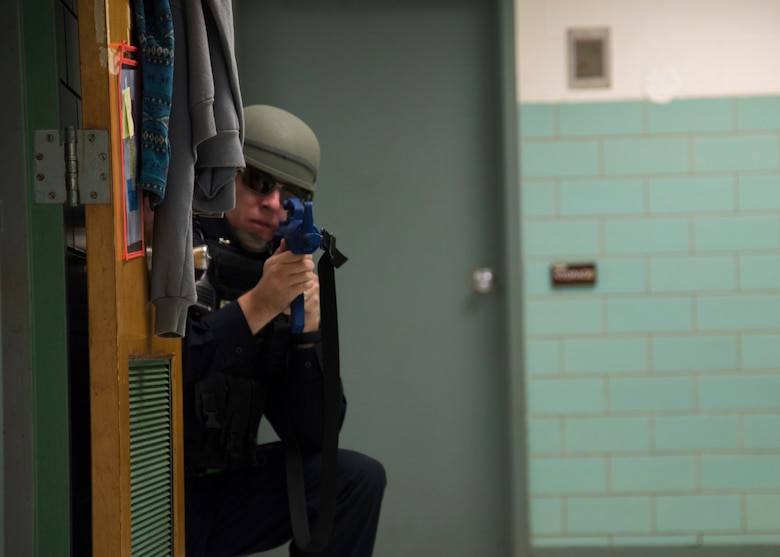 Justin Viens, 436th Security Forces Squadron supervisory police officer, keeps watch down a hallway Oct. 11, 2019, at Dover Air Force Base, Del. Viens strategically positioned himself to continuously scan for threats during an active shooter exercise. (US Air Force Photo by A1C Jonathan Harding)