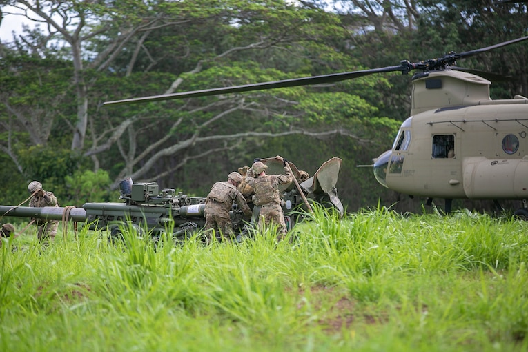 Soldiers work on military equipment next to a helicopter.
