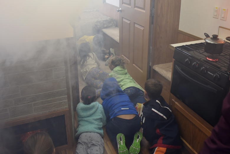 Michael-Anderson Elementary School students practice an evacuation drill inside a smoke trailer simulator during National Fire Prevention Week at Fairchild Air Force Base, Washington, Oct. 7, 2019.