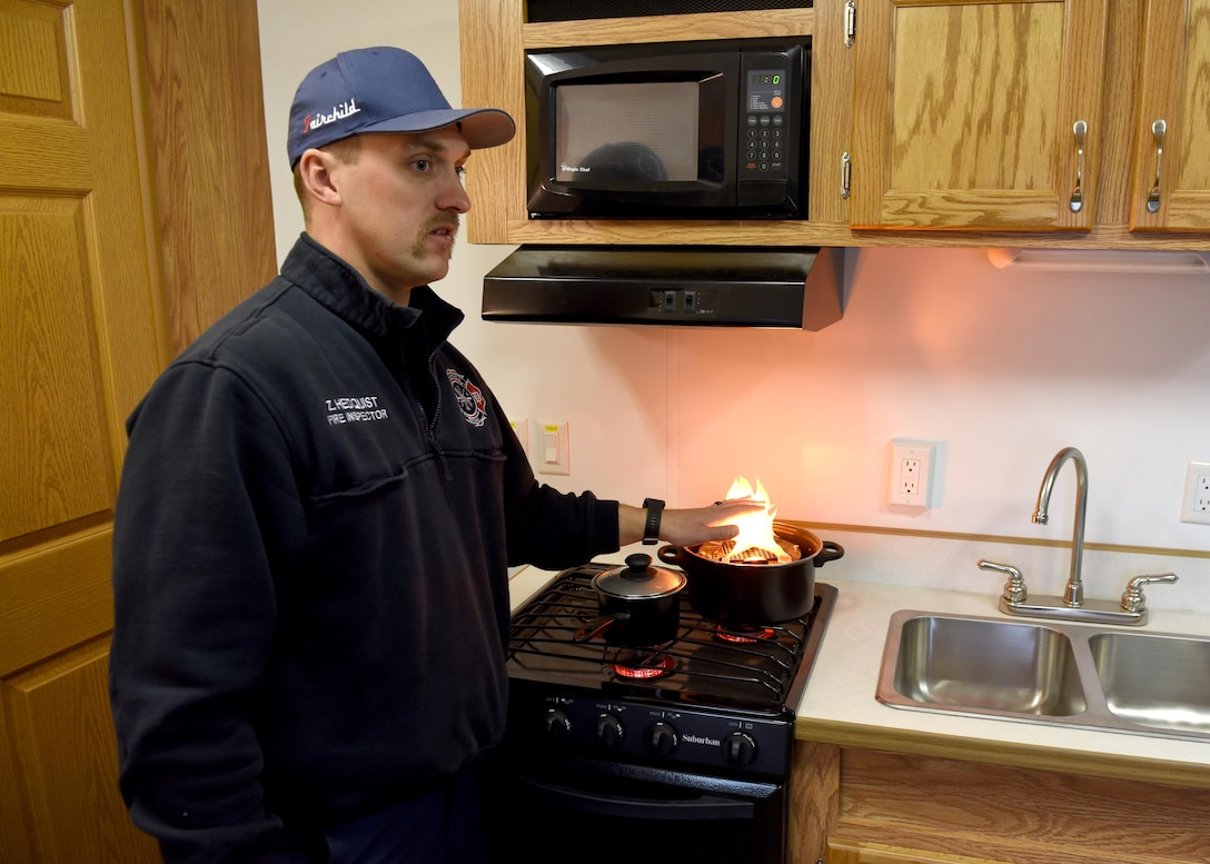 Zachary Hedquist, 92nd Civil Engineer Squadron fire inspector, demonstrates the dangers of leaving a stove top unattended in the smoke trailer simulator at Fairchild Air Force Base, Washington, Oct. 7, 2019.