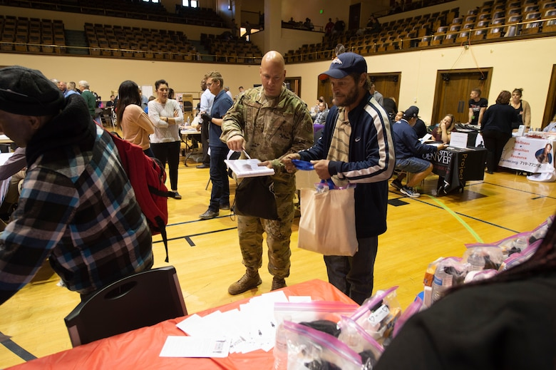 Senior Master Sgt. Michael Keinholz, 21st Communications Squadron flight chief, escorts Rodney, a veteran, through one of the various support agency lines during the 21st annual Homeless Veteran Stand Down at the Colorado Springs City Auditorium, Colorado Springs, Colorado, Oct. 15, 2019. Volunteers were assigned a veteran to engage with throughout the day, providing an opportunity to listen and connect with the veterans. (U.S. Air Force photo by Staff Sgt. Matthew Coleman-Foster)