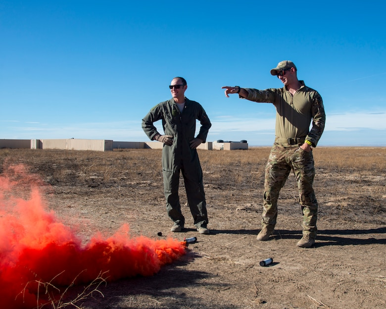 Staff Sgt. David Chorpeninng, 366th Fighter Wing survival, evasion, resistance and escape specialist, explains to Capt. Scott Hatter, 389th Fighter Squadron aircrew how to properly use a MK-124 marine smoke and illumination signal Sept. 26, 2019, at Saylor Creek Bombing Range, Idaho.