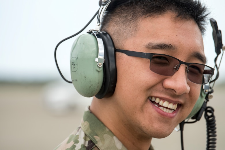 U.S. Air Force Senior Airman Peter Nguyen, a 13th Aircraft Maintenance Unit F-16 Fighting Falcon assistant dedicated crew chief, smiles while marshalling an F-16 during an aviation training relocation at Komatsu Air Base, Japan, Oct. 3, 2019. Capt. Phillip McCoy, a 13th Fighter Squadron F-16 pilot and Komatsu ATR detachment commander, described the ATR participants as hard working, consistent and dedicated to the mission of executing bilateral training sorties regardless of unexpected changes, such as inclement weather experienced during the week-long exercise. The 13th AMU and its Airmen are assigned to Misawa AB. (U.S. Air Force photo by Senior Airman Collette Brooks)
