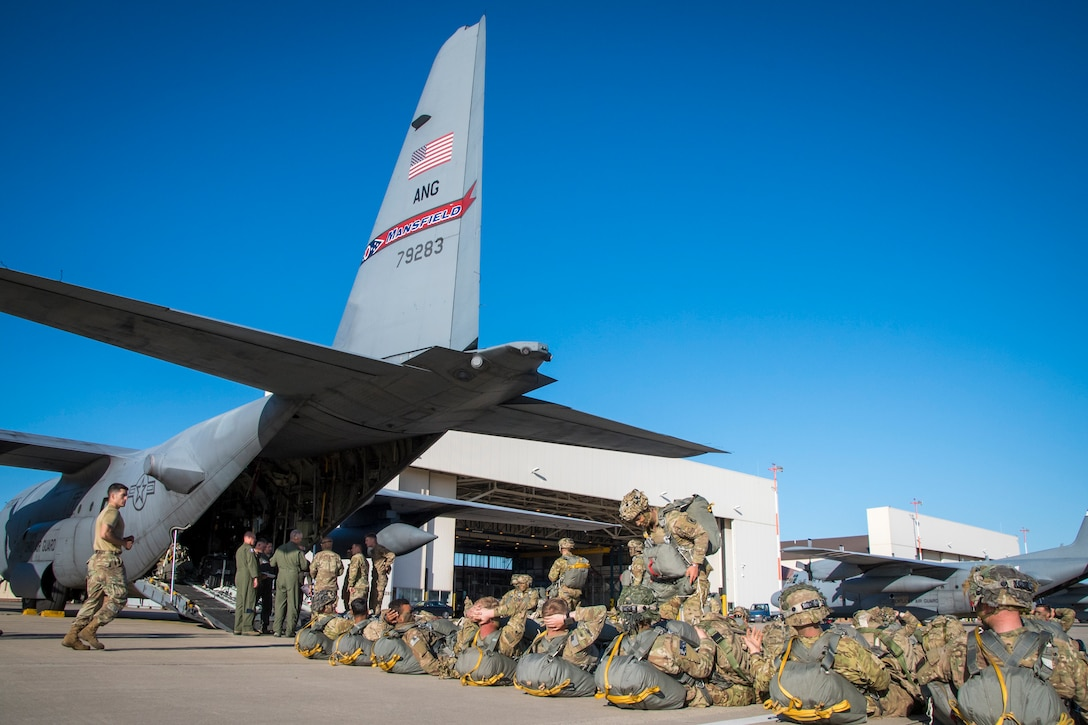 Photo of military members waiting in line to board a C-130