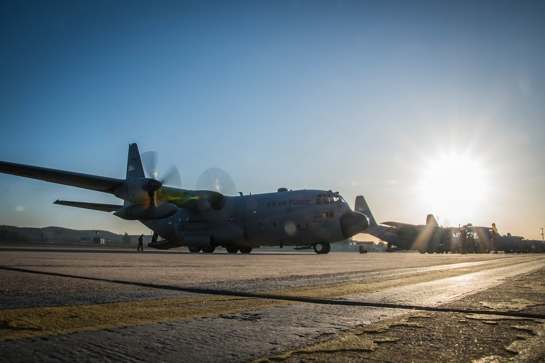 Photo of a C-130 on the flight line with the sun rising