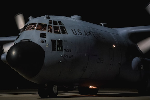 Photo of a C-130 on the flight line early morning.