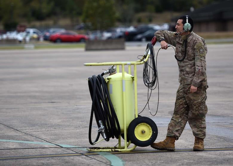 An Airman stands next to a big metal tank.