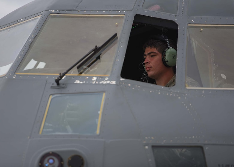 An Airman is seen through the window of a grey plane with a headset on.