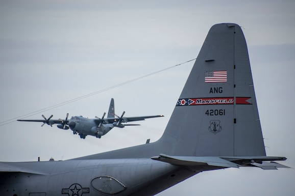 Photo of a C-130 flying over another C-130