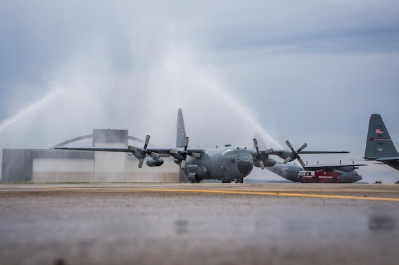 Photo of fire trucks spraying water on a C-130