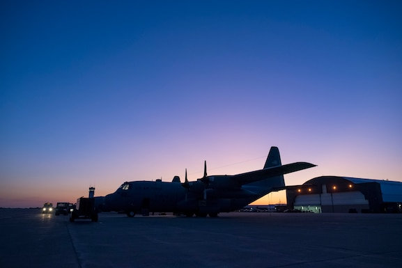Photo of the sun rising over the flight line of C-130H Hercules.