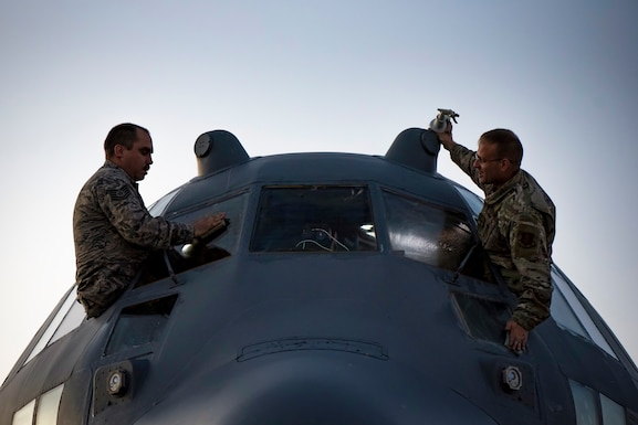 Photo of 2 Airmen cleaning C-130 windows