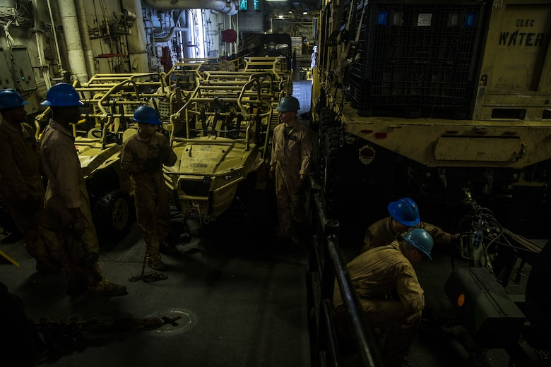 U.S. Marines with the 26th Marine Expeditionary Unit move and secure cargo aboard the amphibious assault ship USS Bataan (LHD 5) during composite training unit exercise in the Atlantic Ocean Oct. 9, 2019. Combat cargo Marines are key members of the team that ensure all gear and equipment is loaded safely and efficiently. (U.S. Marine Corps photo by Cpl. Tanner Seims)