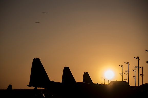 Photo of the sun setting over the aircraft on a flight line