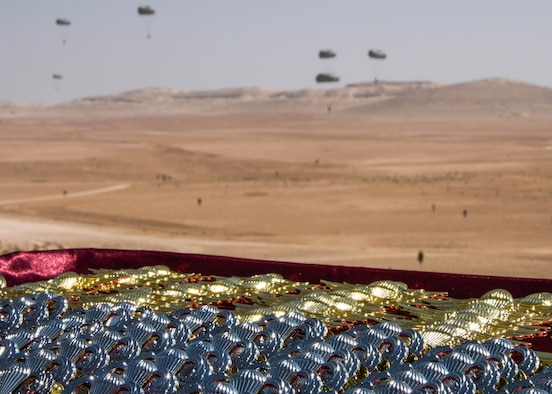 A set of jump wings prepared for the pinning ceremony that takes place after the Friendship Jump remains in focus as the jumper's parachute to the Jordanian ground during Exercise Eager Lion on Sept. 5, 2019.