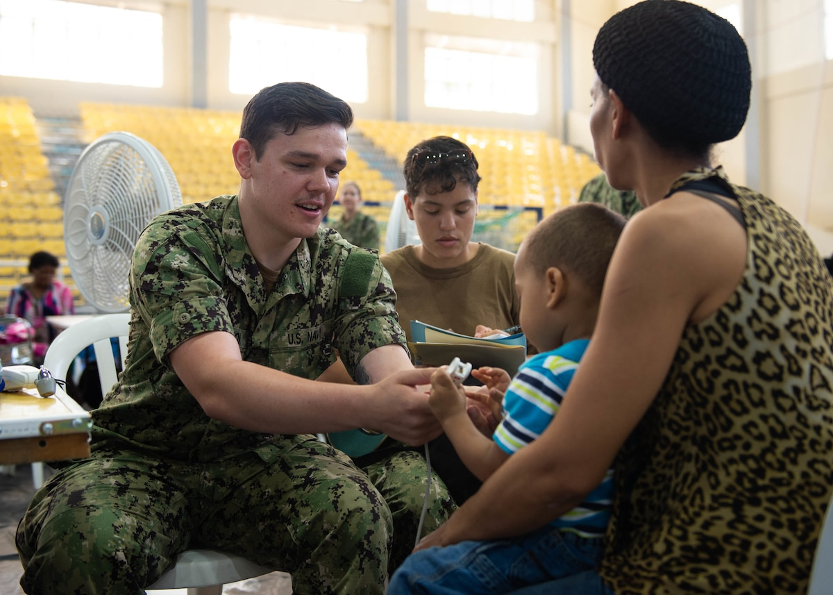 A U.S. Navy Hospital Corpsman checks a boy's vital signs.