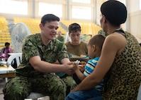 A U.S. Navy Hospital Corpsman checks a boy's vital signs.