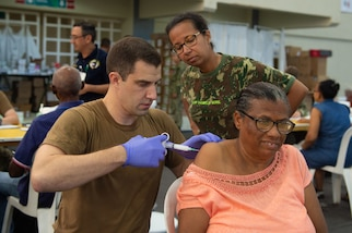 Military doctors administer a steroid shot on a patient.