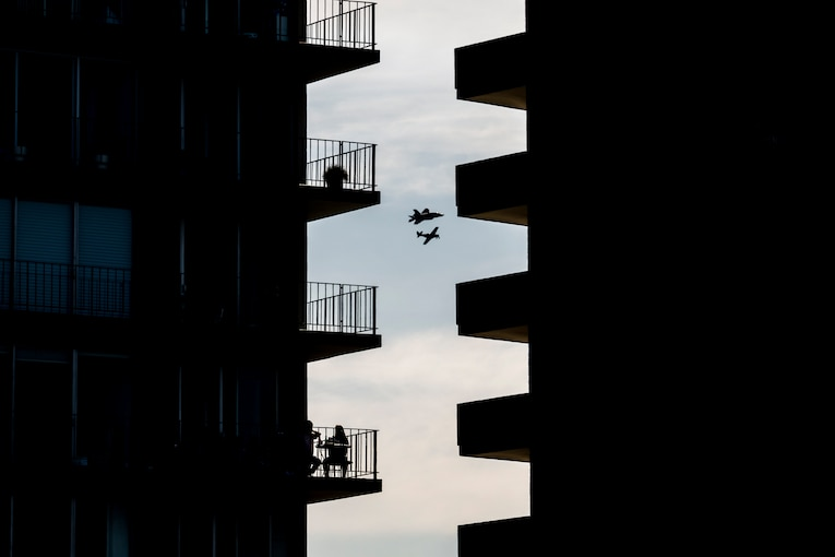 Silhouettes of two aircraft are visible through a zigzag-shaped space between two buildings with protruding balconies.