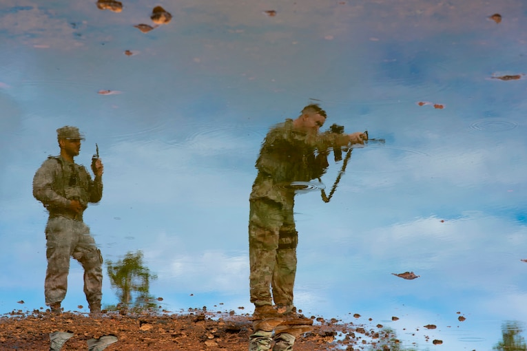 A view of two standing airmen, one pointing a weapon, is reflected in light blue water.
