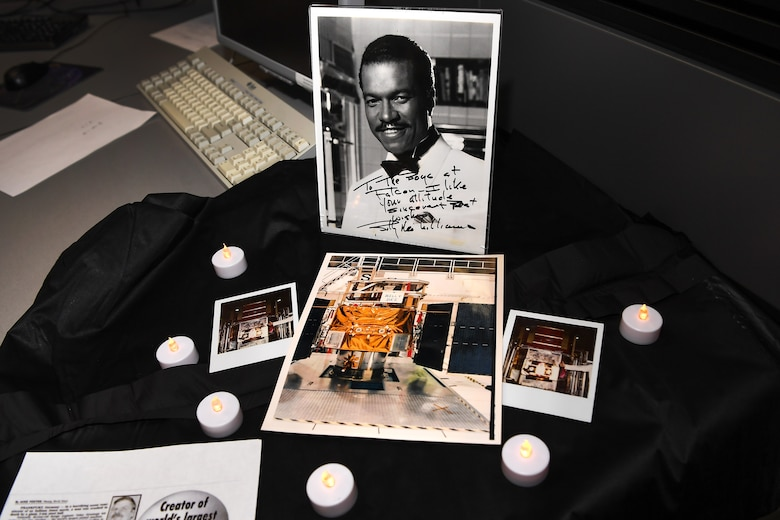 "A picture of actor and singer Billy Dee Williams, along with pictures of a satellite named after him, were displayed at the 2nd Space Operations Squadron floor during the decommissioning of one of its satellites on Schriever Air Force Base, Colorado, Oct. 9, 2019. According to Capt. Jeremy Crossman, 2nd SOPS assistant director of operations, the decommissioned satellite was nick named Billy Dee based on a 2nd SOPS internal joke. The word ""attitude"" in the signed photo is a play on the word altitude, which establishes where the satellite is pointing, a mission critical aspect during a satellite launch. If a satellite's altitude is incorrect during launch, it could end in a non-operational orbit. (U.S. Air Force photo by Katie Calvert)"