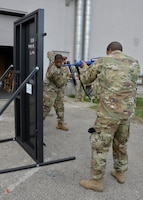 Senior Airman Daryn Weatherspoon, fire team member, 445th Security Forces Squadron, takes a swing at forcing open a metal training door outside the squadron on September 8, 2019 as Staff Sgt. Andrew Swasey, fire team member, looks on. The training, designed to give Airmen the opportunity to practice breaching locked doors, included several types of tools and simulated various team dynamics. (U.S. Air Force photo/1st Lt. Rachel Ingram)