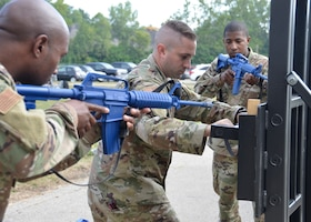 Staff Sgt. Chris Bell, fire team member, Tech. Sgt. Nathan Ellcessor, fire team leader, and Senior Airman Daryn Weatherspoon, fire team member, all with the 445th Security Forces Squadron, demonstrate the proper way to use a tool called a hooligan to force open a locked door September 8, 2019. The demonstration was part of a door-breaching training which included about 30 Airmen and offered hands-on practice with multiple specialized tools. (U.S. Air Force photo/1st Lt. Rachel Ingram)