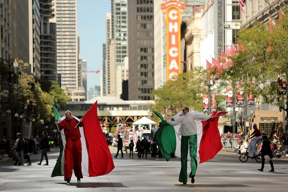 Parade participants walk on stilts, carrying large Italian flags, during the 2019 67th Annual Columbus Day Parade in the City of Chicago, October 14, 2019.