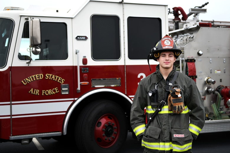 A man stands in front of a fire truck.