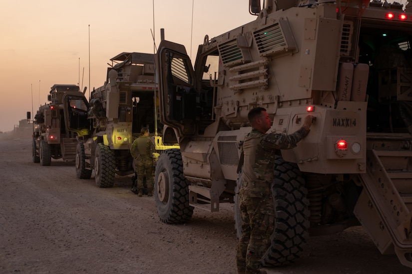 A soldier stands outside of a military vehicle; with other vehicles parked in front.