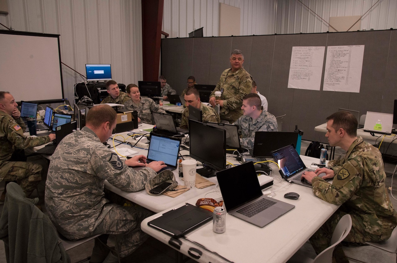 Service members looking at laptops sit around a conference table.