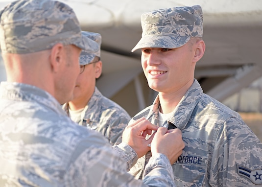 U.S. Air Force Lt. Col. Chris Sharp, 316th Training Squadron commander, pins Airman 1st Class Noah Sharp, a recent linguist graduate, with his job badge at Goodfellow Air Force Base, Texas, Sept. 11, 2019. Noah's father had the honor of pinning him and officially making him a graduate of the linguist course. (U.S. Air Force photo by Airman 1st Class Ethan Sherwood/Released)