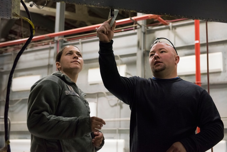 Josh Collins, 402nd Commodities Maintenance Group, aircraft structural mechanic explains to 2nd Lt. Emily Fogel, 366th Maitencance Group, the process of installing a spar repair piece on an F-15E Strike Eagle Oct 4, 2019, at Mountain Home Air Force Base, Idaho. The repair was done in order to preserve the mission readiness of the aircraft. (U.S. Air Force photo by Senior Airman Tyrell Hall)