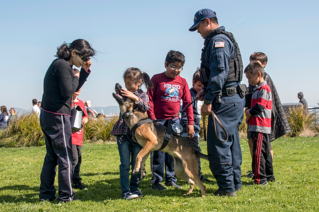 A Coast Guardsman watches as a kid pets a working dog and other civilians gather around.
