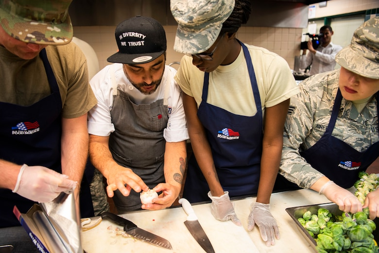 Chef David Viana, USO Celebrity Chef Tour participant, instructs his team The Startled Koalas on the components of their dish for the cooking competition Oct. 15, 2019, at F.E. Warren Air Force Base, Wyo. Along with Viana's team, Chef Justin Sutherland mentored the team Kitchen Regulators and Chef Kevin Scharpf lead Chop It Like It's Hot. (U.S. Air Force photo by Senior Airman Abbigayle Williams)