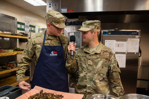 Senior Airman Kyle O'dea, 90th Force Support Squadron missile chef, interviews Airman 1st Class Nathaniel Kooker, 90th FSS food service specialist, about the items he has been preparing during a cooking competition Oct. 15, 2019, at F.E. Warren Air Force Base, Wyo. O'dea was one of the hosts during the competition and provided commentary for the living feed into the dining hall where the judges and fans sat. (U.S. Air Force photo by Senior Airman Abbigayle Williams)
