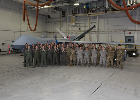 Airmen with the 20th Attack Squadron pose for a group photo in front of an MQ-9 Reaper, at Whiteman Air Force Base, Missouri, June 17, 2019. The 20th ATKS is a geographically separated unit that falls under the 432nd Wing/432nd Air Expeditionary Wing and supports combatant commanders in operations abroad. (U.S. Air Force photo by Airman 1st Class Parker J. McCauley)