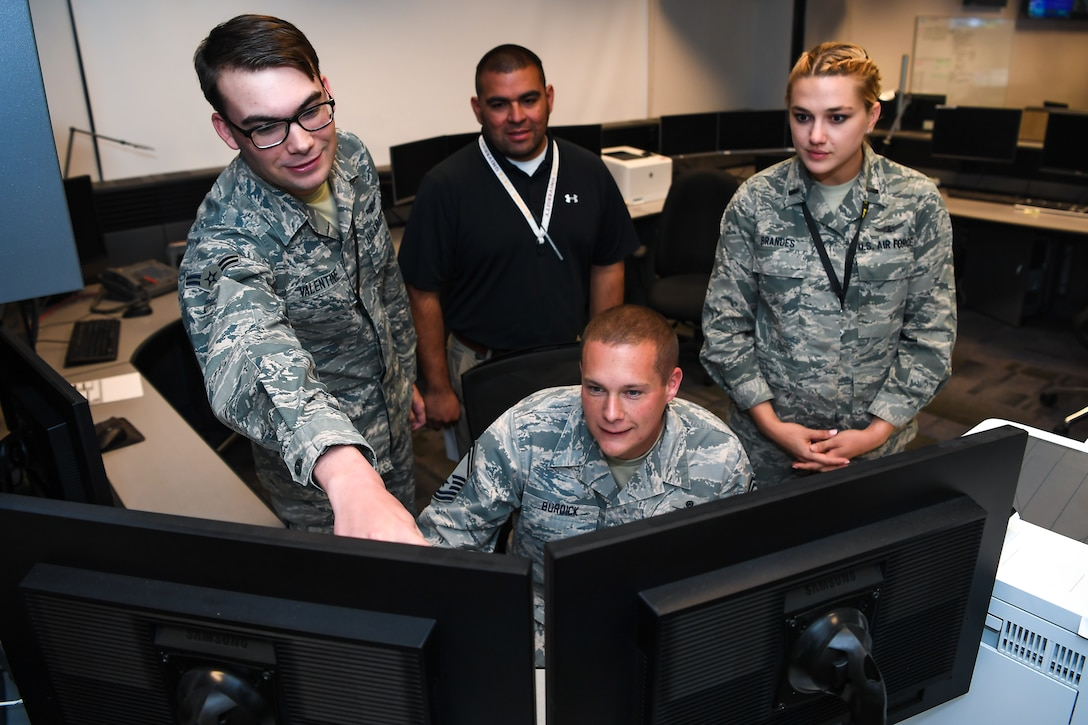 Senior Master Sgt. Blair Burdick II, center, 2nd Space Operations Squadron superintendent, gives the last command to decommission Satellite Vehicle Number-38, while Airman 1st Class David Valentine, left, 2nd SOPS satellite system operator; Arturo Martínez, center back, Boeing engineer; and 1st Lt. Kristina Brandes, right, 2nd SOPS chief bus system analyst, observe on Schriever Air Force Base, Colorado, Oct. 9, 2019. The squadron surprised Burdick, who will retire from the Air Force in March 2020, with the opportunity to decommission the 22-year-old satellite from service. This SVN-38 is being decommissioned to make way for GPS-III satellites, the first one was launched on December 2018. (U.S. Air Force photo by Katie Calvert)