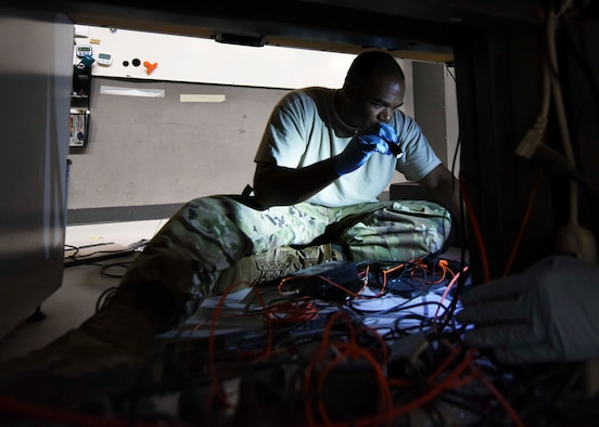 Master Sgt. Thaddaus Zeno, 609th Expeditionary Air Communications Squadron tactical transmission systems section chief, performs communication maintenance and IT infrastructure upgrades on the Combat Operations Division floor at the Combined Air Operations Center, Al Udeid Air Base, Qatar, Sept. 28th, 2019. The CAOC relinquished air power command and control operations to the Total Force 609th Air Support Squadron at Shaw Air Force Base in South Carolina for a 24-hour period, allowing the 609th EACOMS to perform their mission. (U.S. Air Force photo by Staff Sgt. Soo Kim)