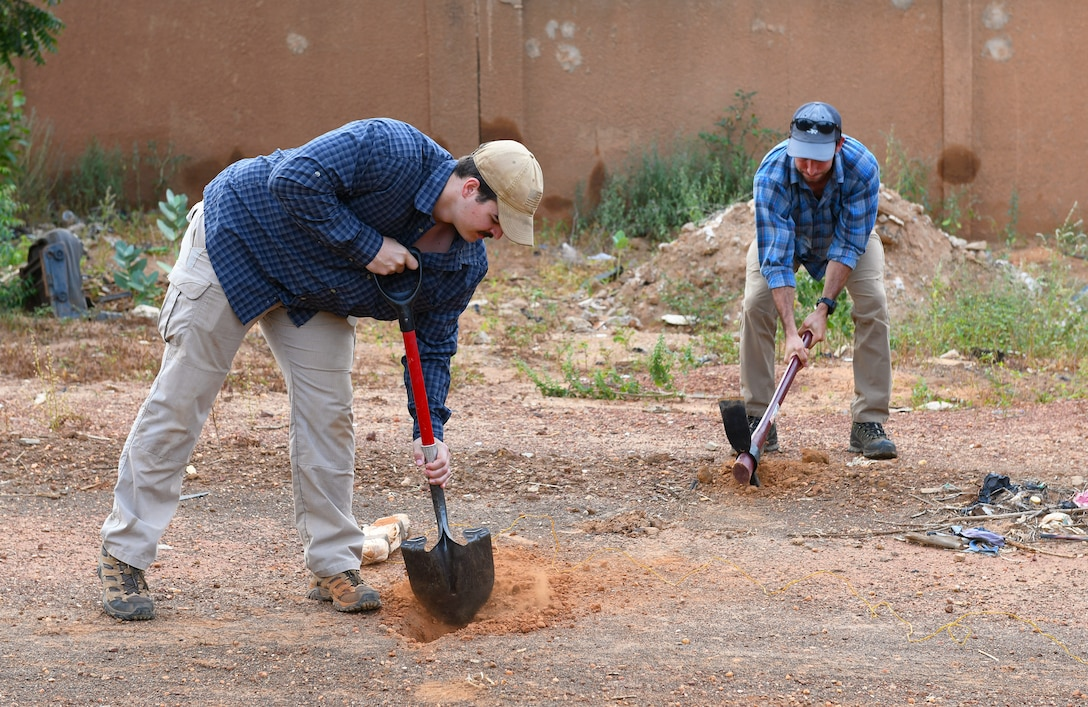U.S. Air Force Senior Airmen Caleb Love, left, and Michael Augustus, 768th Expeditionary Air Base Squadron Explosive Ordnance Disposal team members, bury a training improvised explosive device during an IED Awareness Course for the Forces Armées Nigeriennes (Nigerien Armed Forces) in Niamey, Niger, Oct. 11, 2019. During this week-long course, the FAN learned how to locate and react to an IED, how set up a cordon and the procedures to clear the area. (U.S. Air Force photo by Staff Sgt. Alex Fox Echols III)