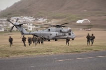 U.S. Marines with Charlie Company, 1st Battalion, 3rd Marine Regiment, conduct a simulated air assault on Landing Zone Eagle from a CH-53E Super Stallion with Heavy Marine Helicopter Squadron 463, part of exercise Island Marauder on Marine Corps Base Hawaii, Kaneohe Bay, Sept. 25, 2019. The Island Marauder exercise is a training event during which Marines conducted different scenarios while testing new technology on the battlefield. (U.S. Marine Corps photo by Ashley Calingo)