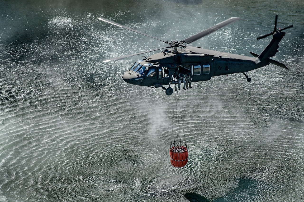 A helicopter flies over a body of water with a bucket suspended underneath by a cable.
